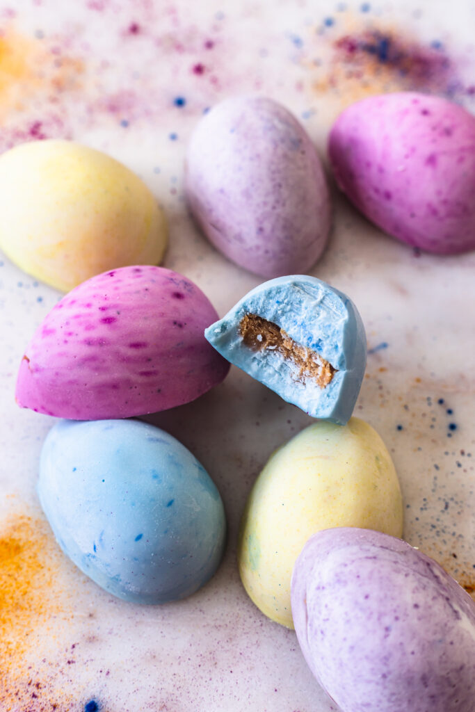 white chocolate colored eggs stacked on top of each other, one with a bite taken out of it to reveal the peanut butter filling