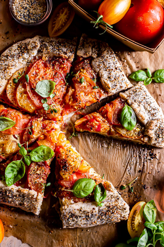 close up of a sliced tomato galette with a  basket of tomatoes beside it and fresh basil leaves