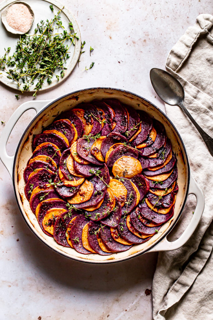 a round skillet with roasted purple and orange sweet potatoes in a colored pattern with fresh thyme and linen napkin and spoon on the side