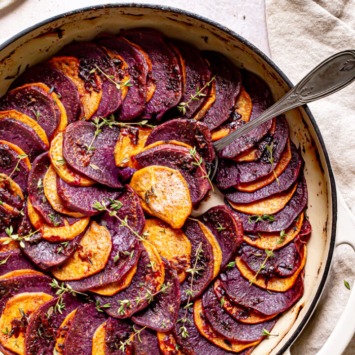 a round skillet with roasted purple and orange sweet potatoes in a colored pattern with fresh thyme and linen napkin and spoon scooping out some potatoes