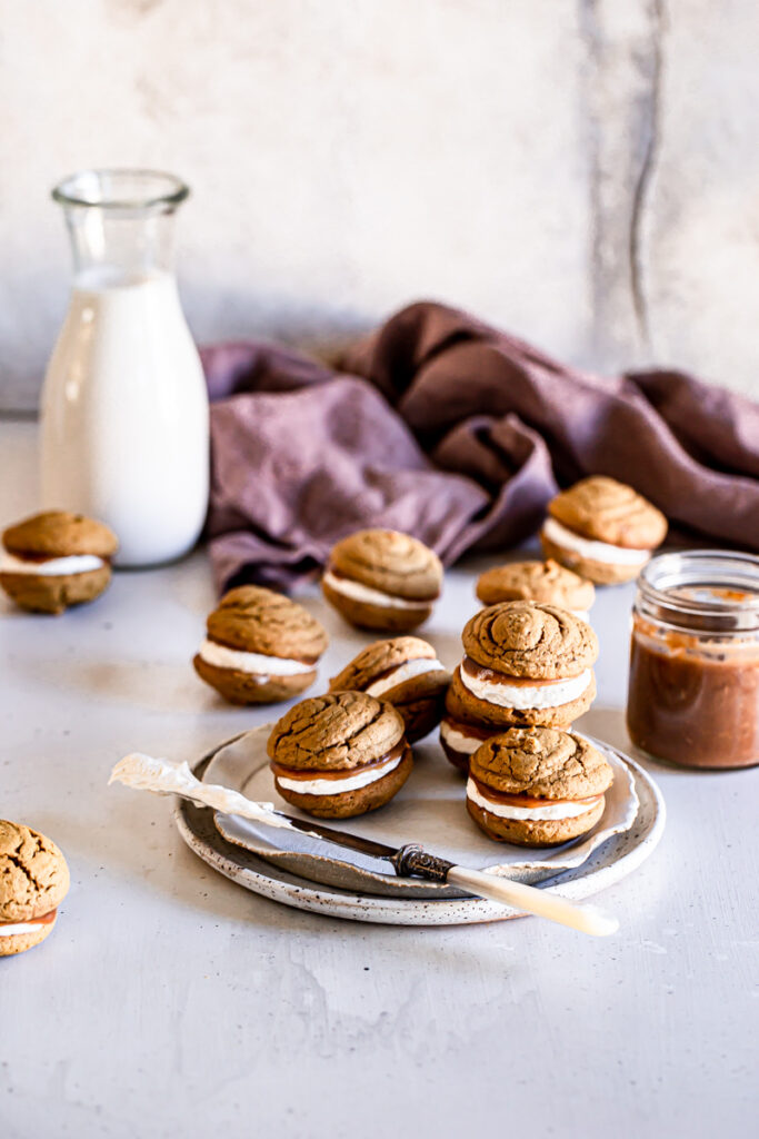 whoopie pies on a plate with a jug of almond milk and jar of apple butter