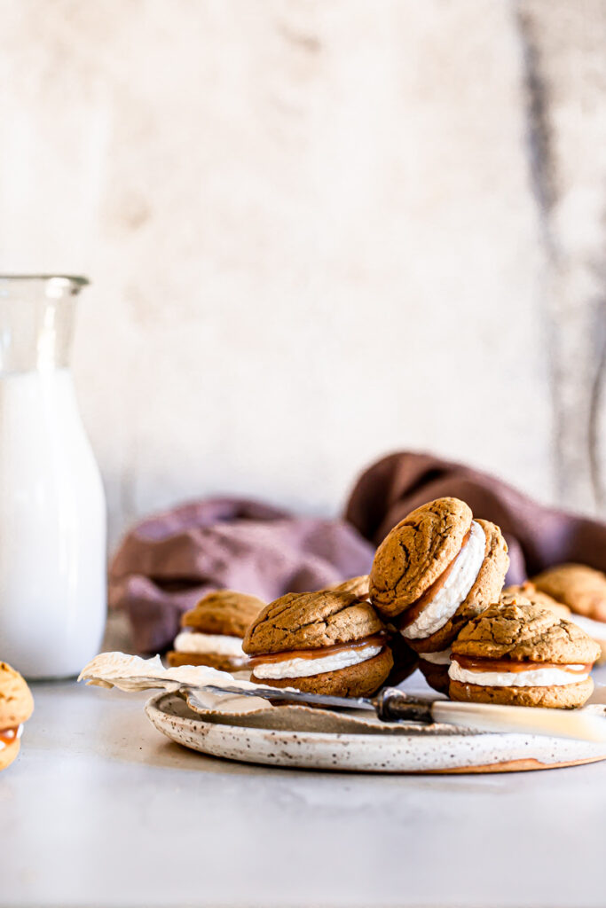 apple butter whoopie pies piled on a plate with a jug of almond milk in the background