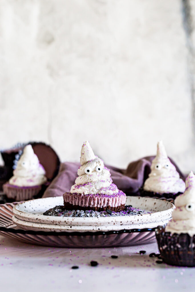 cheesecake ghost on a plate in the middle of the frame with 3 other cheesecakes out of focus in front and behind with a purple linen towel in the background