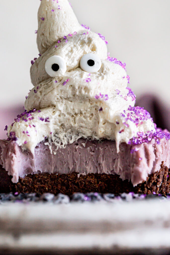 vegan cheese cake with a chocolate crust and purple vegan cashew cheesecake layer topped with a buttercream frosting ghost with candy eyes and purple sprinkles