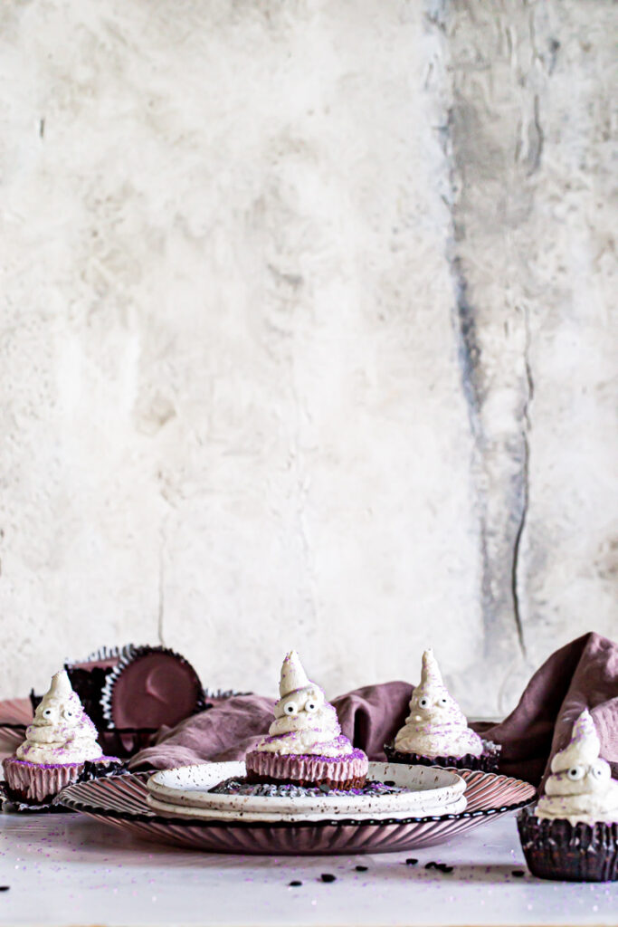 a far away image of mini cheesecake cups with buttercream ghosts on top and a purple linen towel in the background
