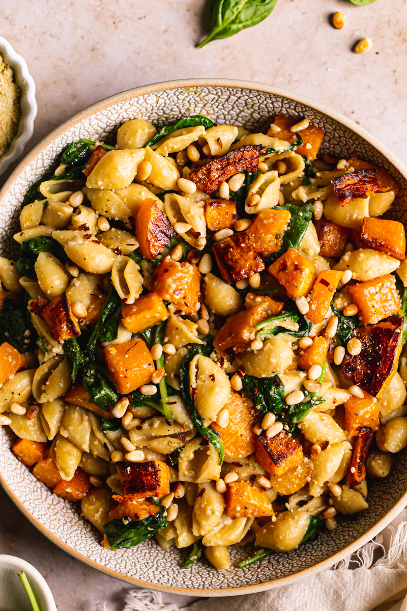 a close up shot of the pasta in a bowl tossed with butternut squash and spinach garnished with vegan parmesan cheese and toasted pine nuts