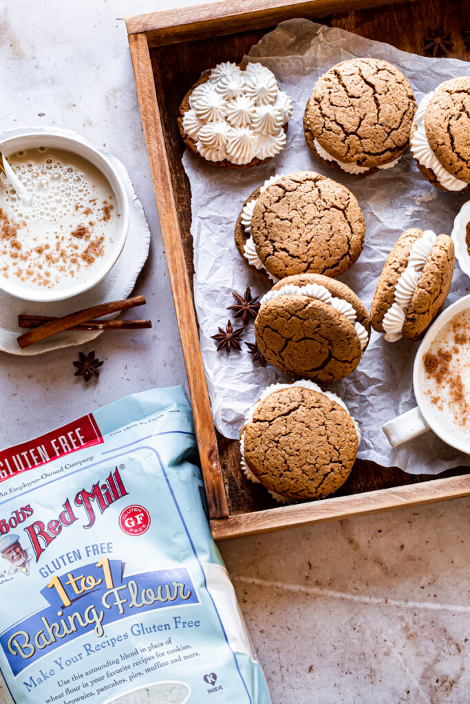 a wooden box with a mug of dairy free egg nog and 6 gingerbread sandwich cookies with a bag of Bob's Red Mill gluten-free 1:1 baking flour