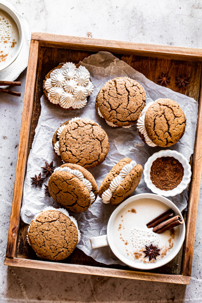 a wooden box with a mug of dairy free egg nog and 6 gingerbread sandwich cookies