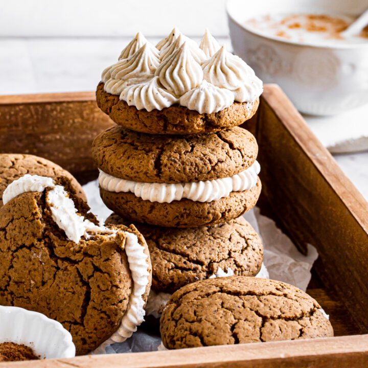three gingerbread sandwich cookies stacked on top of one another, the top one showing the piped buttercream filling