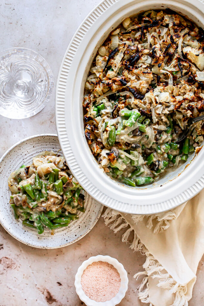 green bean casserole in a casserole dish with some spooned out onto a plate on the side