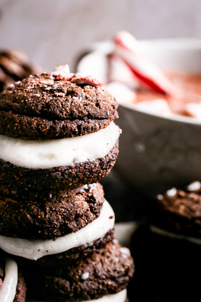 close up shot of hot cocoa Whoopie pies with a cup of hot cocoa in the background
