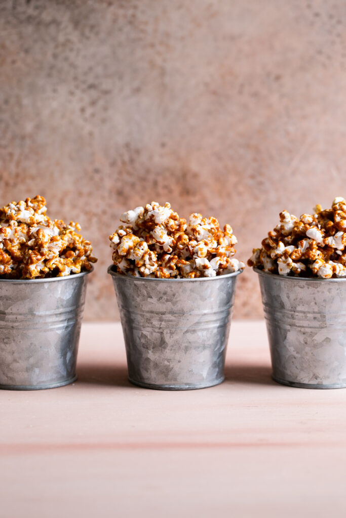 three buckets of caramel popcorn lined up next to each other