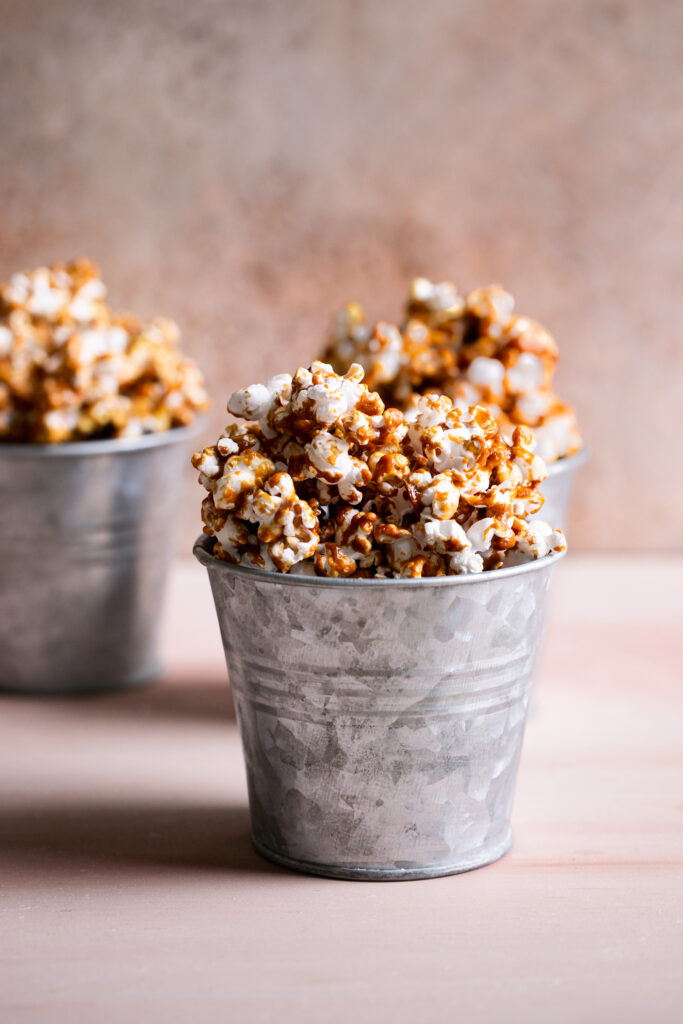 three buckets of caramel popcorn, one in the foreground and two blurred in the back