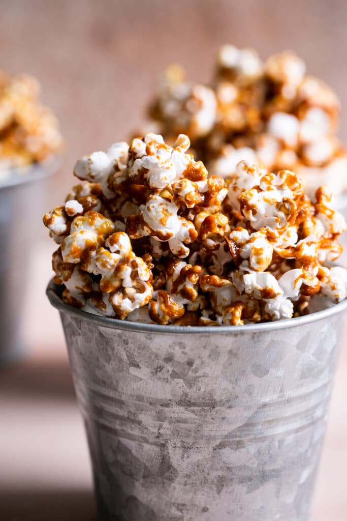 a close up shot of one of the buckets of caramel popcorn