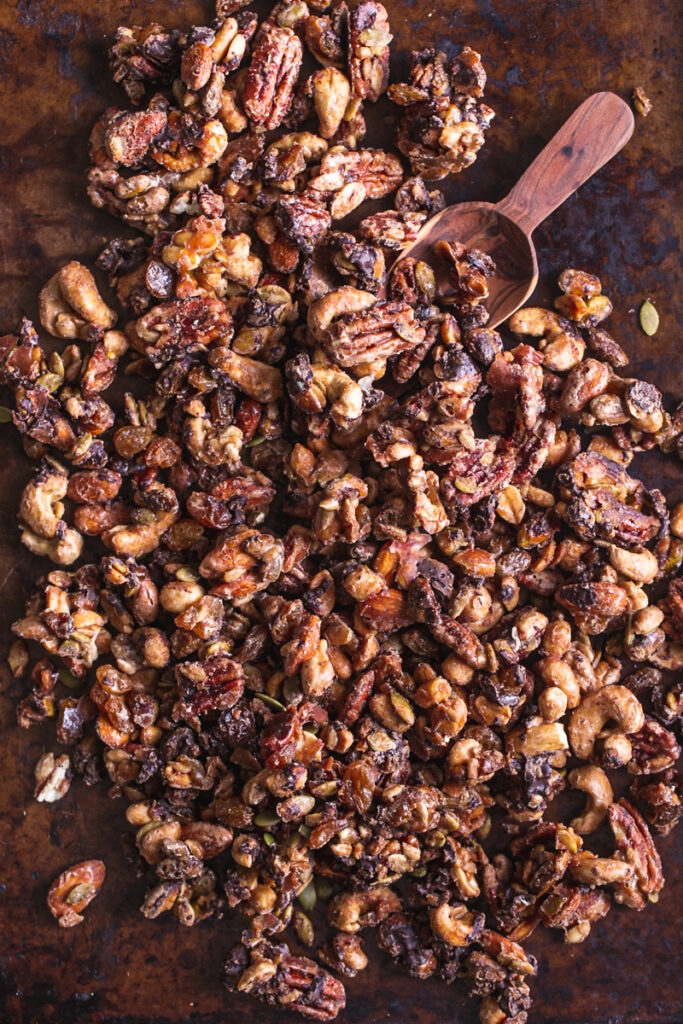 trail mix on a baking sheet with a wooden scoop