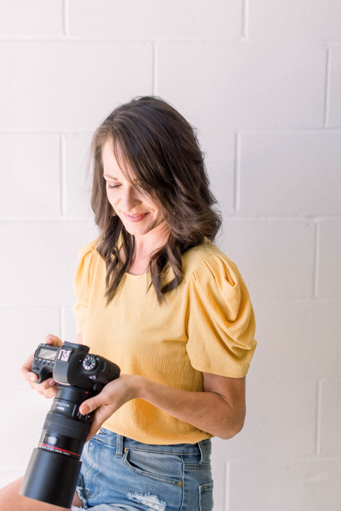 Gina Fontana sitting on a stool wearing a yellow top looking down at her canon camera to preview images she took