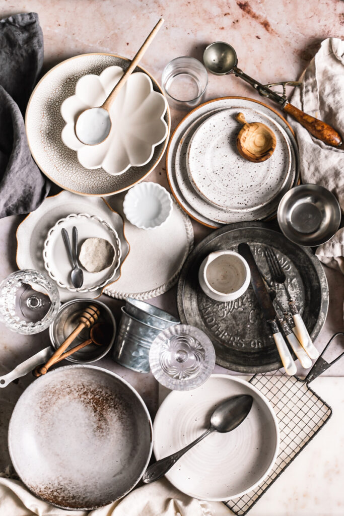 a photo of a bunch of different props I use in food photography, bowls, plates, spoons, napkins, glasses