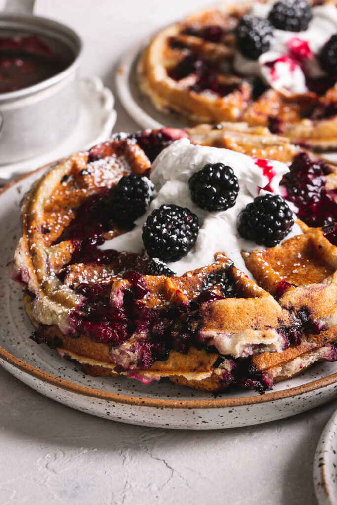 close up side view of a plate of blackberry waffles with more in the background and a pot of blackberry syrup