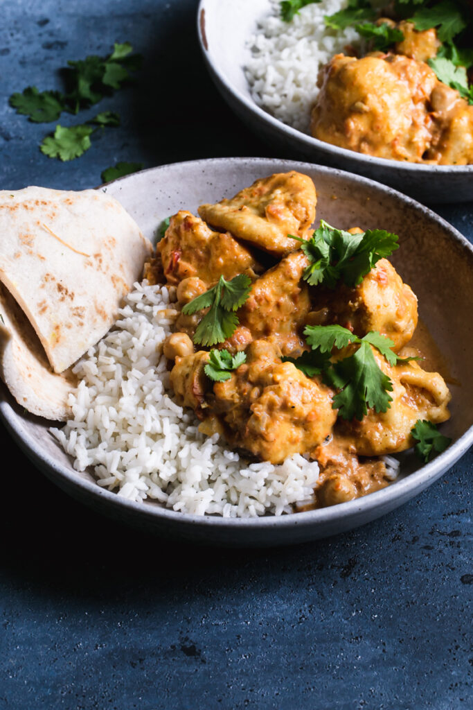 side view of two bowls of rice with breaded cauliflower tossed in a vegan Indian butter sauce garnished with fresh cilantro and a side serving of naan