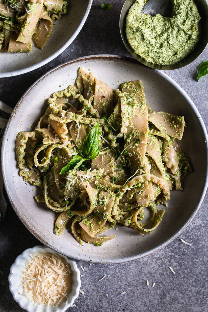 a close up of a bowl of olive pesto pasta garnished with a basil leaf a bowl of olive pesto and vegan parmesan cheese beside the bowl of pasta