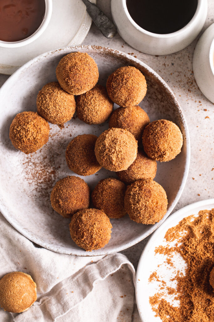 a bowl of grain-free, gluten-free, vegan, naturally sweetened churro donut holes with a bowl of cinnamon coconut sugar beside it with a donut hole in it