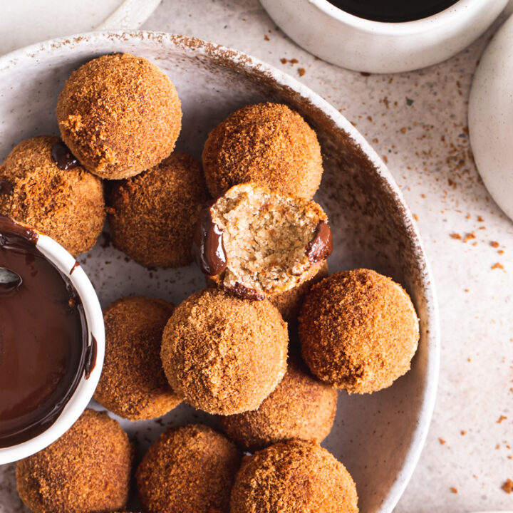 an overhead view of gluten-free, grain free, vegan, naturally sweetened churro donut holes with a bowl of melted chocolate for dipping and one of the donut holes with a bite taken out of it