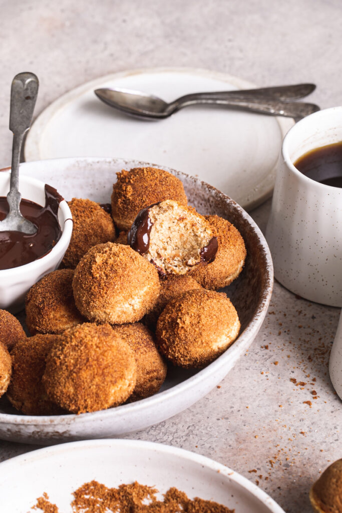 a side view of gluten-free, grain free, vegan, naturally sweetened churro donut holes with a bowl of melted chocolate for dipping and one of the donut holes with a bite taken out of it