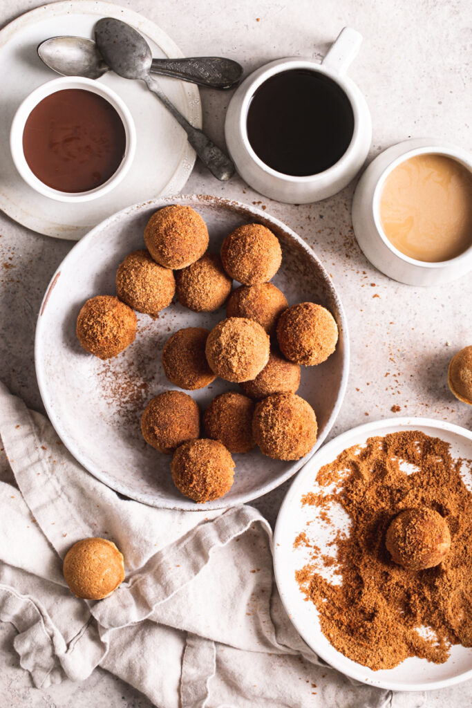 a bowl of grain-free, gluten-free, vegan, naturally sweetened churro donut holes with a bowl of cinnamon coconut sugar beside it with a donut hole in it, a bowl of melted chocolate for dipping and two mugs of coffee