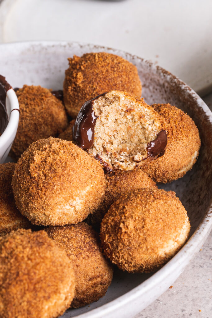 a close up side view of gluten-free, grain-free, vegan, naturally sweetened churro donut holes, one with a bite taken out of it