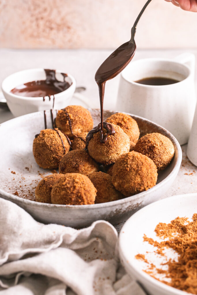 a side view of gluten-free, grain-free, vegan, naturally sweetened churro donut holes with a mug of coffee and a bowl full of melted chocolate in the background and a drizzle of chocolate from a spoon on one of the donut holes