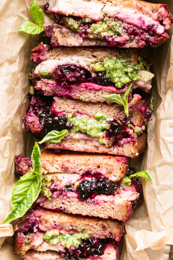 a flatlay image of sliced vegan blackberry pesto grilled cheese stacked together in a loaf pan