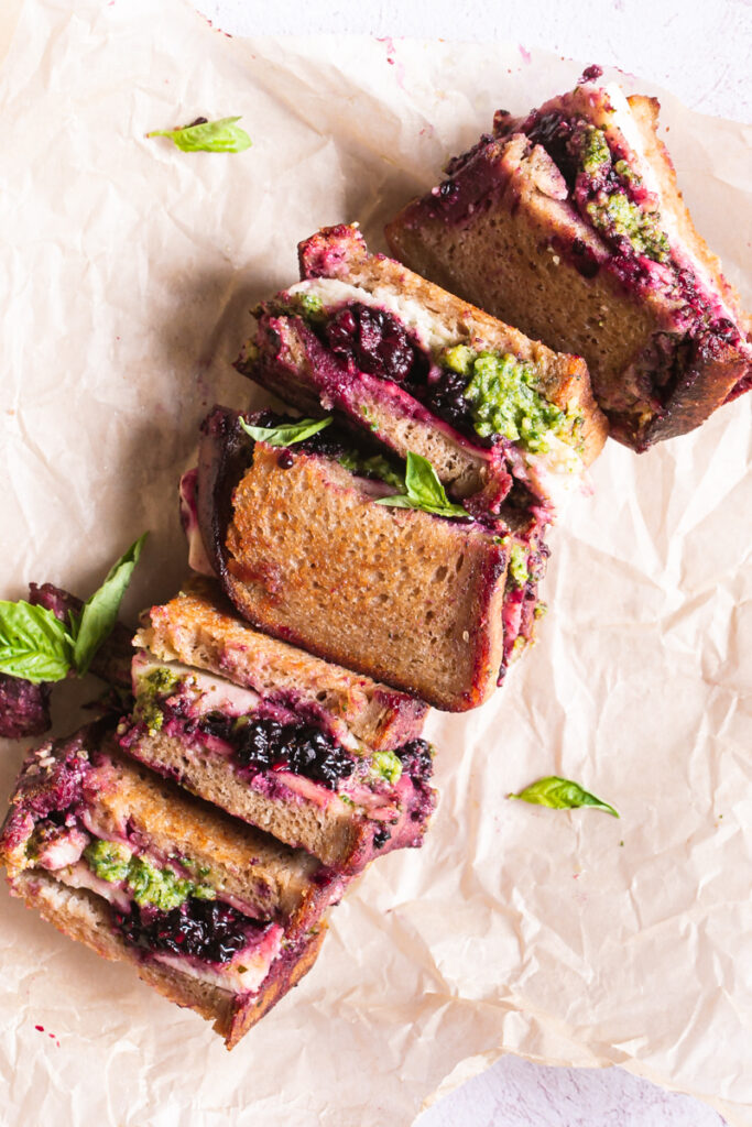 vegan blackberry pesto grilled cheese sandwich halves on a piece of parchment paper