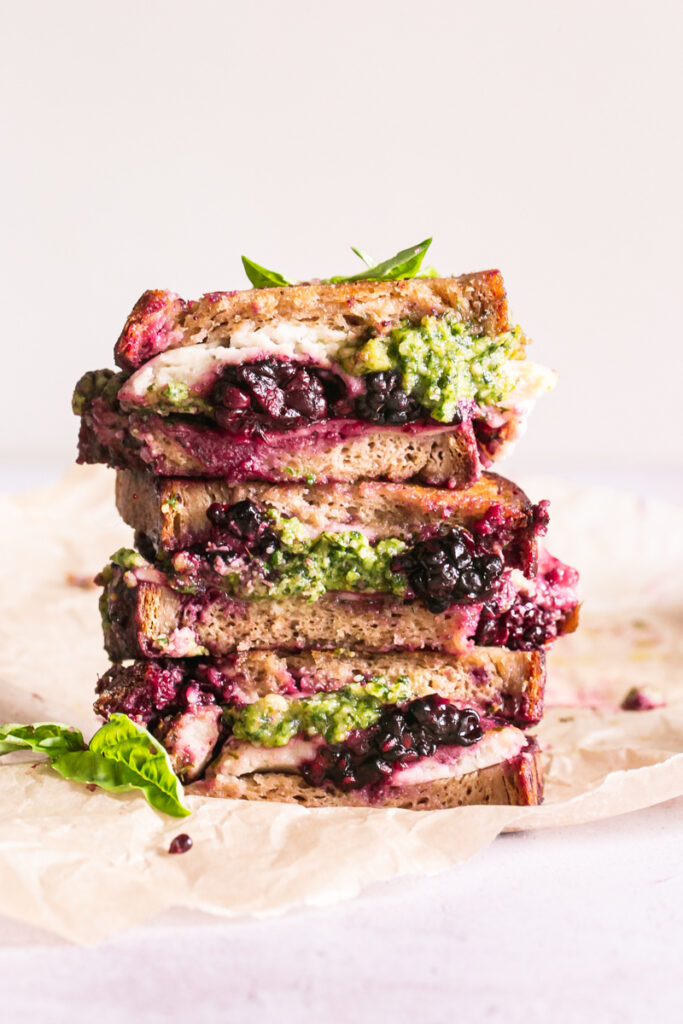 vertical image of vegan blackberry pesto grilled cheese sandwich stacked on top of one another