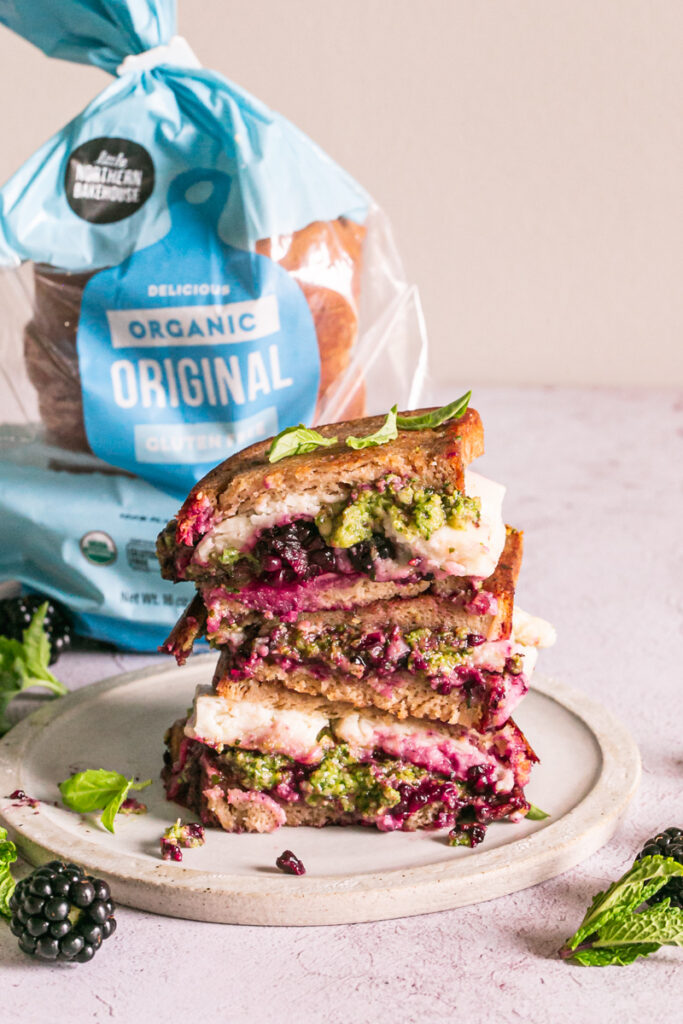 vertical image of vegan blackberry pesto grilled cheese sandwich stacked on top of one another and a loaf of little northern bakehouse bread in the background