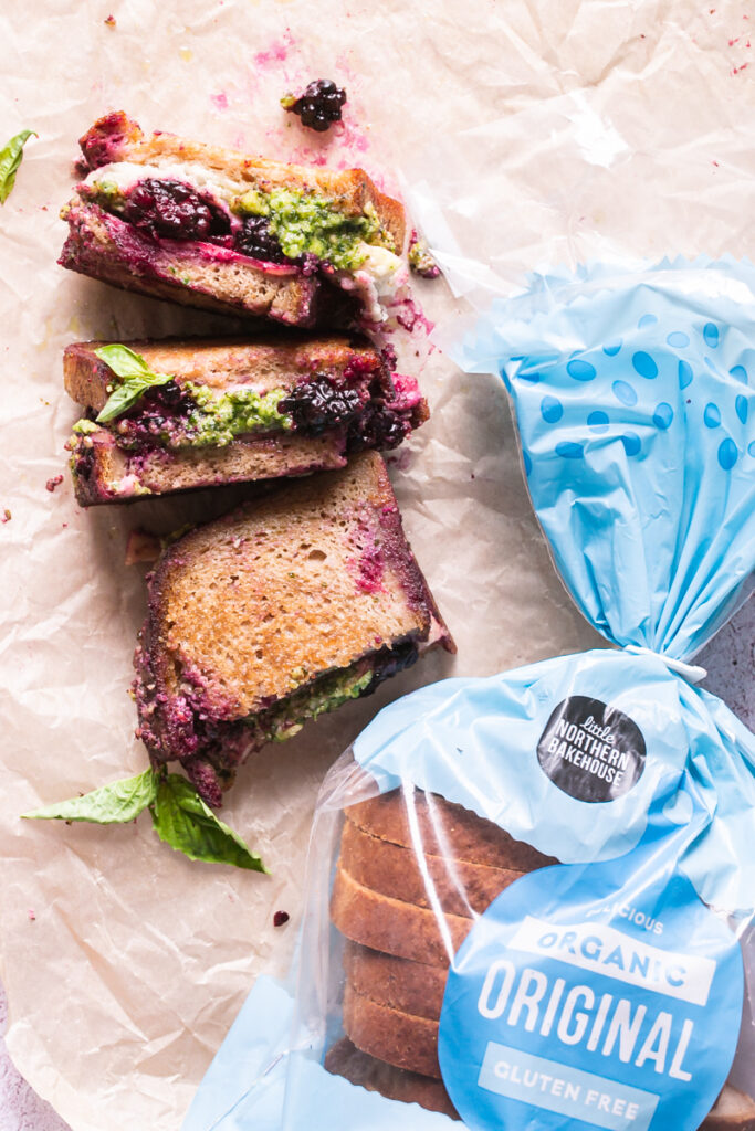 vegan blackberry pesto grilled cheese sandwich halves on a piece of parchment paper with a loaf of little northern bakehouse bread next to it