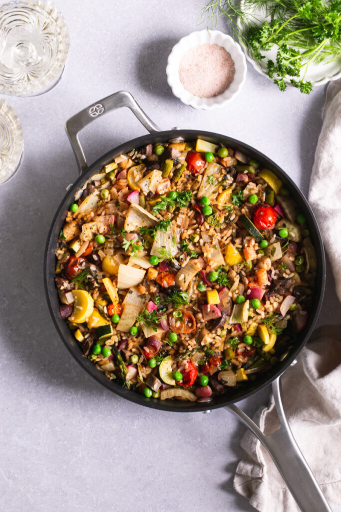 calphalon saute pan with prepared vegetable paella a bowl of salt, plate of herbs, and two glasses of wine next to it