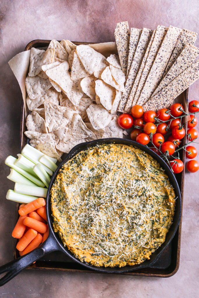 a castiron skillet of spinach artichoke dip surrounded by crackers and veggies