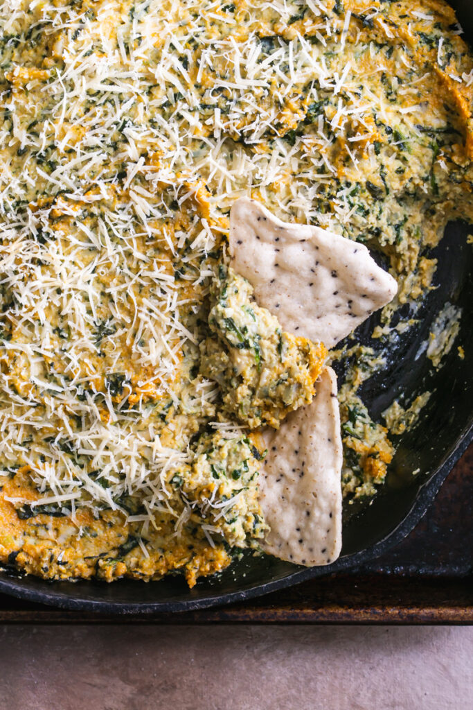 a close up of spinach artichoke dip with 2 tortilla chips