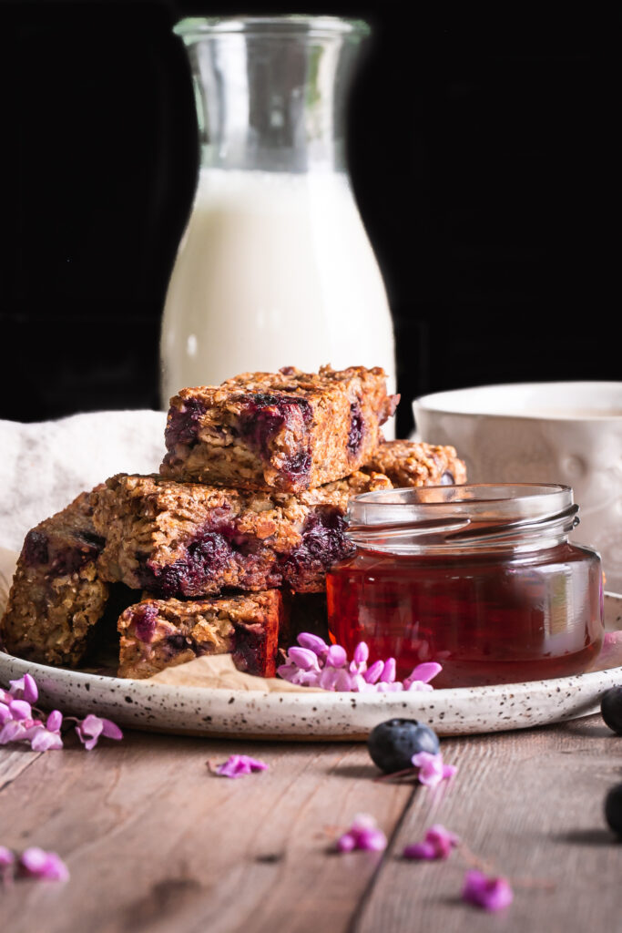 Blueberry Oatmeal French Toast Sticks on a plate with a jar of maple syrup beside it and a cup of coffee and jug of almond milk in the background