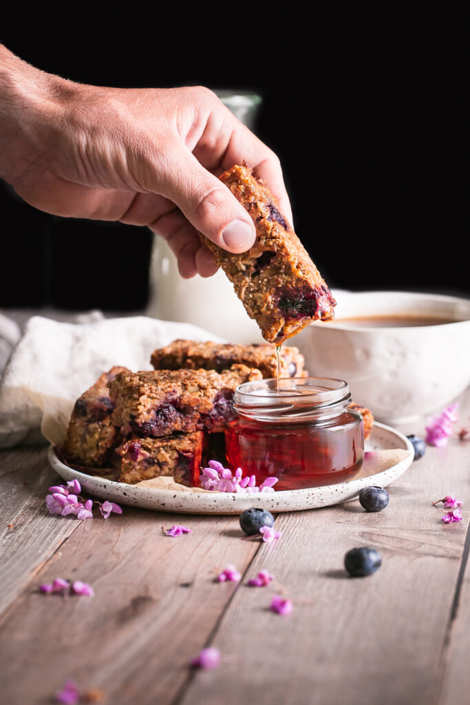 Blueberry Oatmeal French Toast Sticks on a plate one in hand being dipped in a jar of maple syrup with a jar of maple syrup beside it and a cup of coffee and jug of almond milk in the background