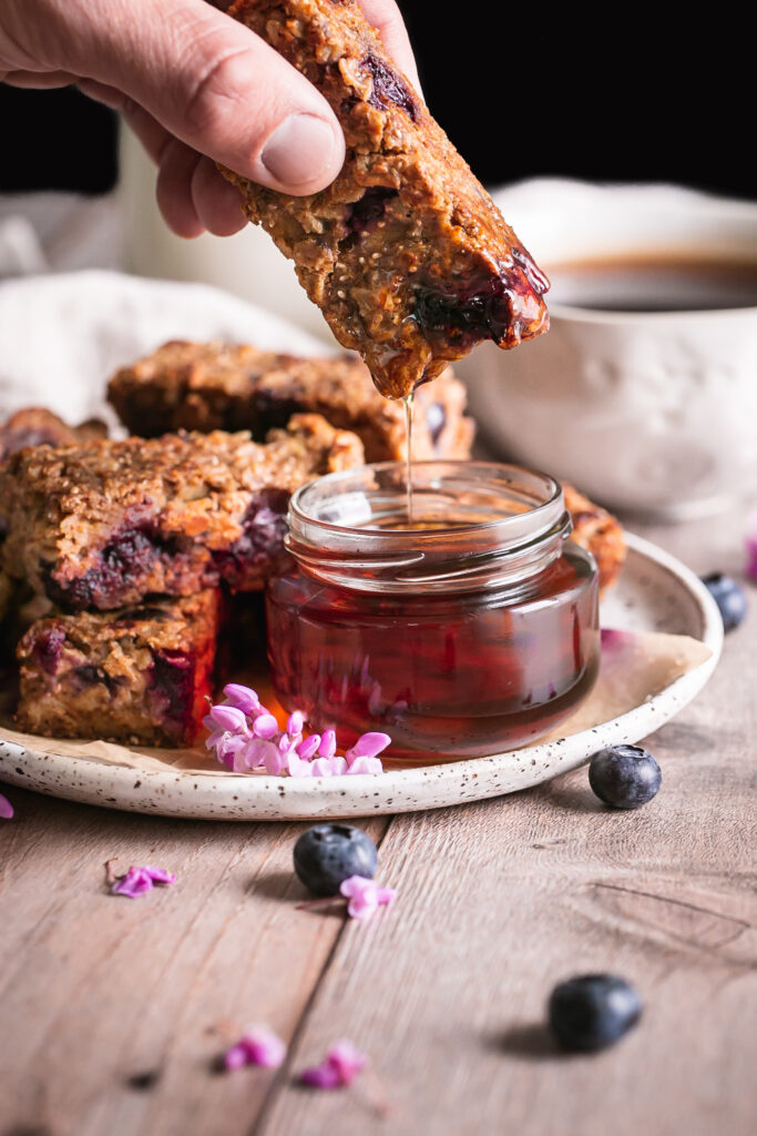 close up of Blueberry Oatmeal French Toast Sticks on a plate one in hand being dipped in a jar of maple syrup with a jar of maple syrup beside it and a cup of coffee and jug of almond milk in the background
