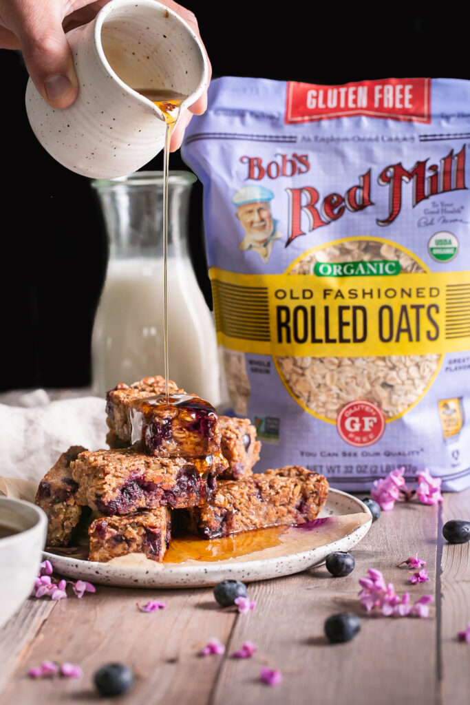 head on view of Blueberry Oatmeal French Toast Sticks piled on top of one another pouring maple syrup over them with a bag of Bob's Red Mill Organic Old Fashioned Rolled Oats in the background