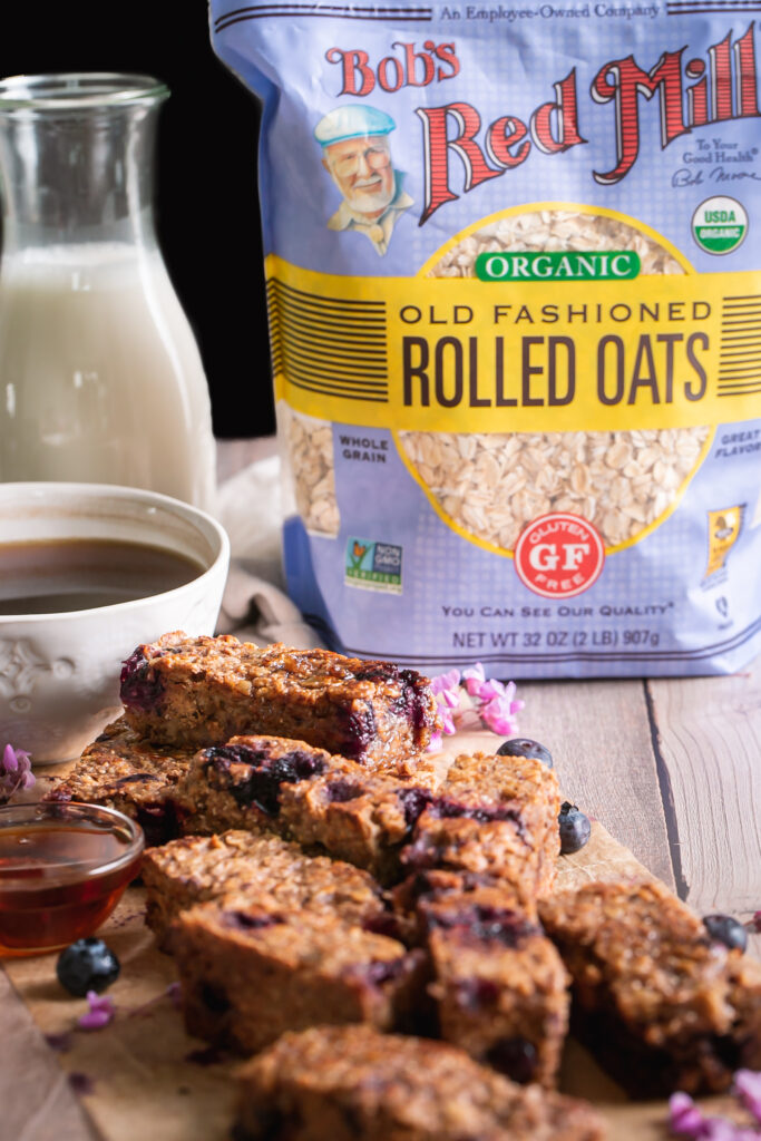 head on view of Blueberry Oatmeal French Toast Sticks piled on top of one another with a bag of Bob's Red Mill Organic Old Fashioned Rolled Oats in the background