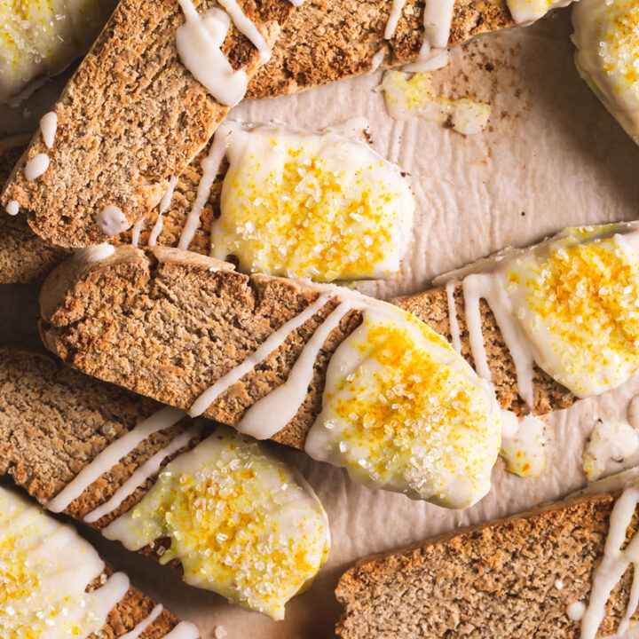 lemon vanilla biscotti piled on top of each other on top of a piece of parchment paper dipped in coconut butter and sprinkled with sparkling sugar and turmeric for color