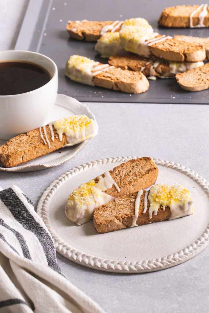 two lemon vanilla biscotti on a plate with a cup of coffee and another biscotti behind it and a cookie sheet of biscotti in the background