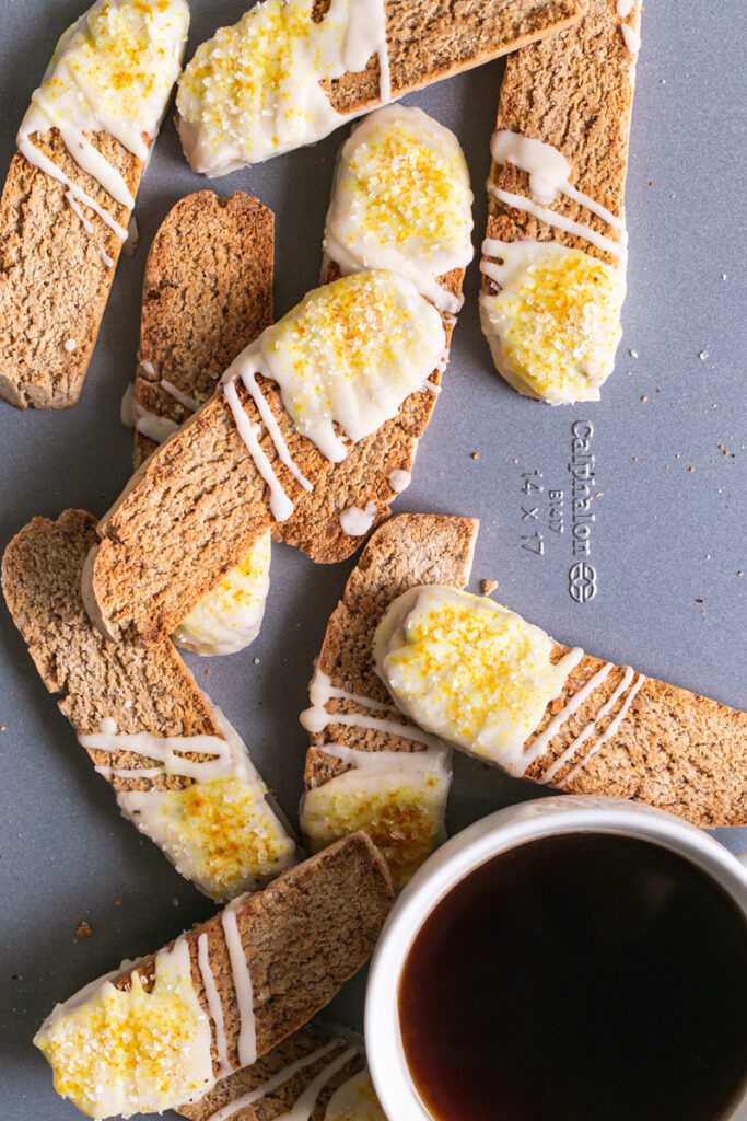 lemon vanilla biscotti piled on top of each other on a Calphalon cookie sheet with a cup of coffee