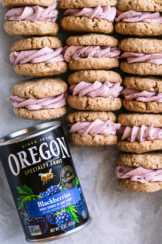 oatmeal sandwich cookies with blackberry cream filling laid in a tray all lined up with the cream filling showing with a can of Oregon canned blackberries in the bottom left corner