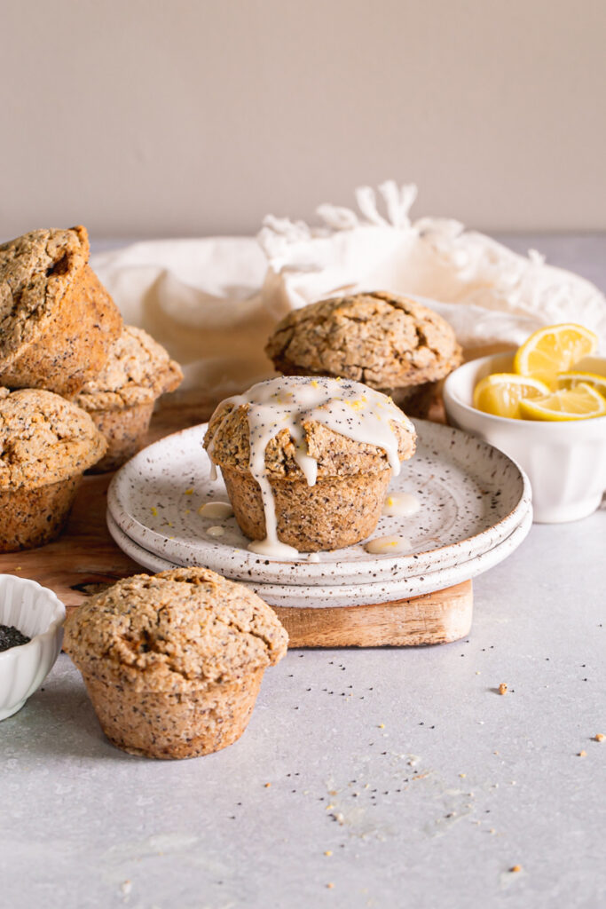 head on shot of lemon poppy seed muffins with one on a plate drizzled with lemon glaze and a bowl of lemons in the background