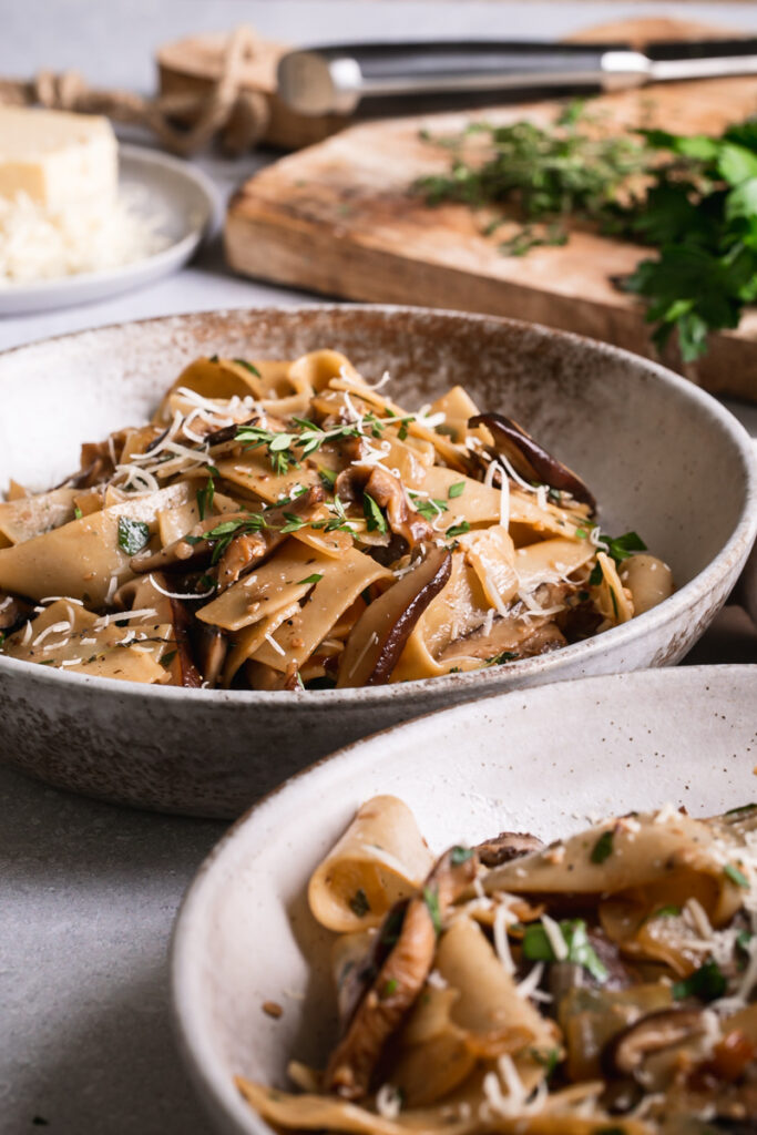 side view of two bowls of gluten-free pappardelle with wild mushroom Ragù