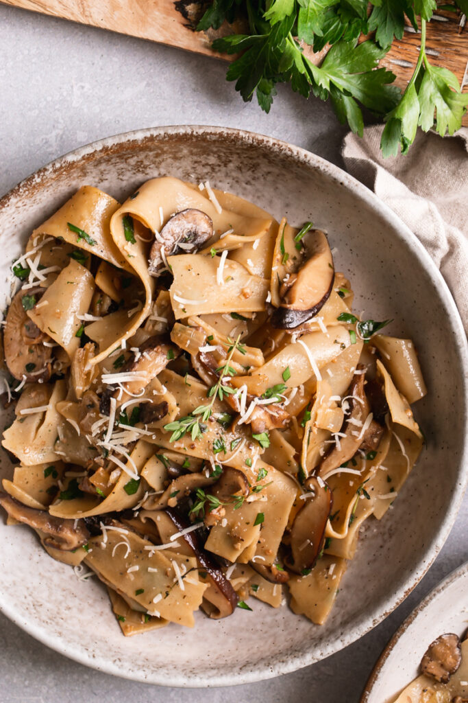a close up of gluten-free pappardelle with wile mushroom Ragù in a bowl